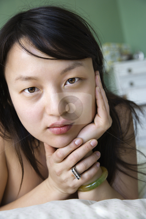 Young Asian woman. stock photo, Portrait of pretty young Asian woman lying in bed with head on hands making eye contact. by Iofoto Images