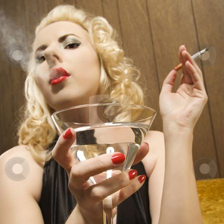 Retro woman portrait. stock photo, Attractive Caucasian woman holding a martini and smoking a cigarette. by Iofoto Images