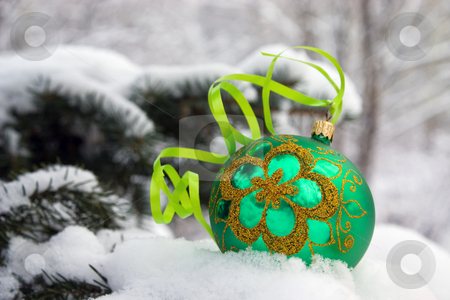 Christmas-tree. stock photo, A green christmas bauble sitting in a bed of snow. by Yury Ponomarev