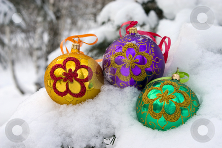 Christmas time. stock photo, Three color christmas baubles sitting in a bed of snow. by Yury Ponomarev