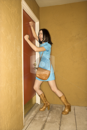 Woman pounding at door. stock photo, Caucasian young adult woman in retro clothing pounding fists on door and yelling. by Iofoto Images