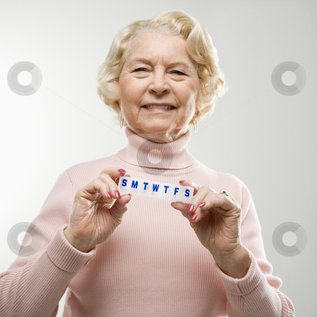 Woman holding pill box. stock photo, Caucasian senior woman holding pill box and smiling at viewer. by Iofoto Images