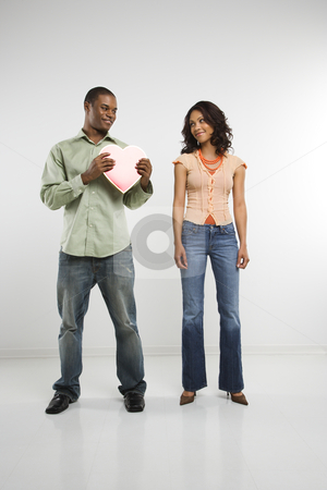 Couple with valentine heart. stock photo, Studio shot of multiethnic couple giving each other valentine heart. by Iofoto Images