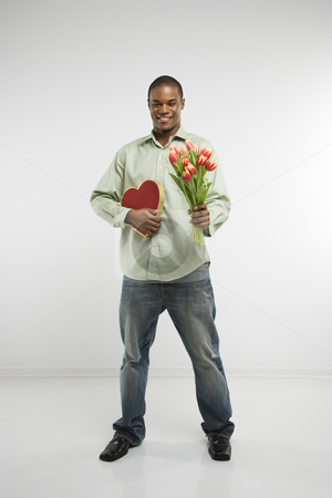 Man holding gifts. stock photo, Studio shot of African-American man holding valentine heart and bouquet of tulips smiling and looking at viewer. by Iofoto Images