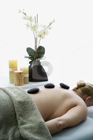 Hot stone massage. stock photo, Caucasian middle-aged woman lying on massage table with hot stones on her back. by Iofoto Images
