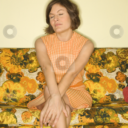 Woman sitting on sofa. stock photo, Pretty Caucasian mid-adult woman sitting on colorful retro sofa with arms crossed and eyes closed. by Iofoto Images