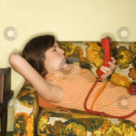 Woman on telephone. stock photo, Pretty Caucasian mid-adult woman lying on colorful retro sofa with arm behind head holding red telephone receiver. by Iofoto Images