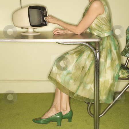 Woman dialing television. stock photo, Side view of Caucasian mid-adult woman wearing green vintage dress sitting at 50's retro dinette set turning old televsion knob. by Iofoto Images