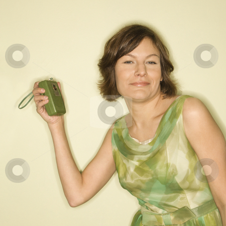 Woman with retro radio. stock photo, Pretty Caucasian mid-adult woman wearing green vintage dress with handheld radio smiling at viewer. by Iofoto Images