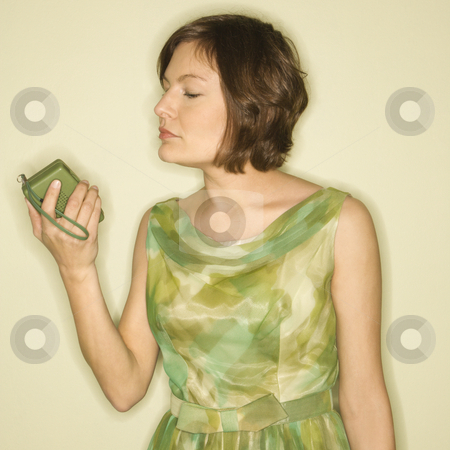 Woman with handheld radio. stock photo, Pretty Caucasian mid-adult woman wearing green vintage dress looking at handheld radio. by Iofoto Images