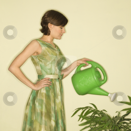 Woman watering plant. stock photo, Pretty Caucasian mid-adult woman wearing vintage dress watering houseplant with green watering can. by Iofoto Images
