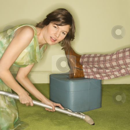 Woman vacuuming carpet. stock photo, Unhappy pretty Caucasian mid-adult woman kneeling and vaccuuming carpet around male feet resting on foot stool. by Iofoto Images