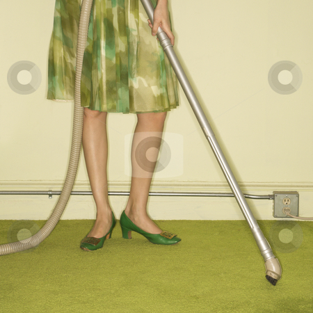 Woman vacuuming rug. stock photo, Close-up of Caucasian female legs with vacuum extension against green retro carpet. by Iofoto Images