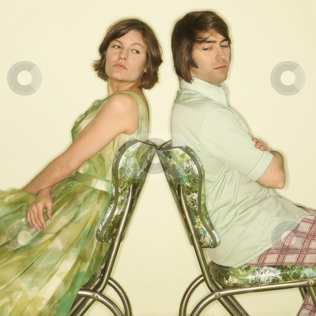 Couple back to back. stock photo, Caucasian mid-adult couple wearing vintage clothing sitting back to back in green vinyl chairs with arms crossed looking angry. by Iofoto Images