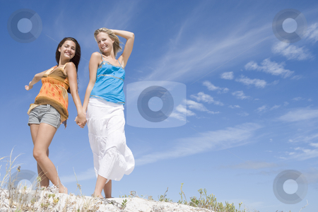 Two young women relaxing at beach stock photo, Two young women relaxing at beach against blue sky by Monkey Business Images