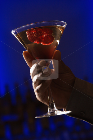 Hand holding martini. stock photo, African American man's hand holding holding martini mixed drink with raspberry fruit against glowing blue background. by Iofoto Images