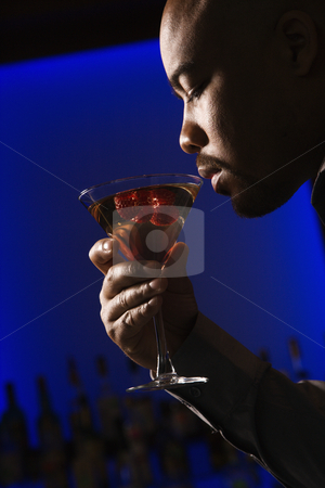 Man drinking martini. stock photo, Profile of African American man drinking martini in bar against glowing blue background. by Iofoto Images