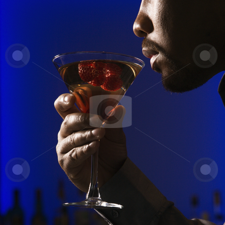 Man drinking martini. stock photo, Close up profile of African American man drinking martini in bar against glowing blue background. by Iofoto Images