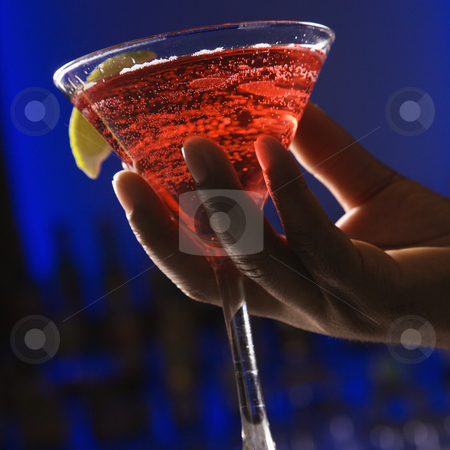 Hand holding martini. stock photo, African American male hand holding martini in bar against glowing blue background. by Iofoto Images