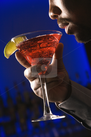 Man drinking martini. stock photo, African American man bringing martini up to lips in bar against glowing blue background. by Iofoto Images