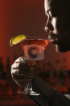 Man drinking martini. stock photo, African American man drinking martini in bar against glowing red background. by Iofoto Images