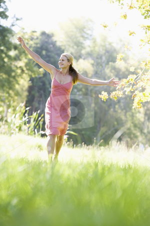 Young woman walking through countryside stock photo, Young woman walking through summer fields by Monkey Business Images