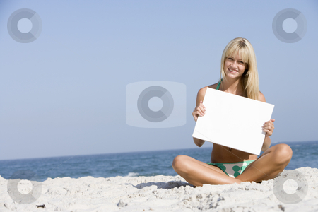 Woman on beach holding blank card stock photo, Woman on beach holding blank card by Monkey Business Images