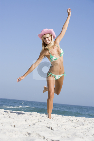 Young woman on beach holiday stock photo, Young woman on beach holiday wearing cowboy hat by Monkey Business Images