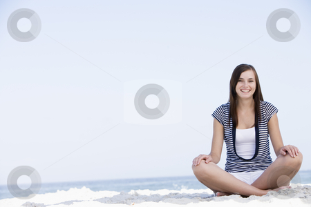 Young woman sitting on beach stock photo, Young woman sitting on beach with ocean behind by Monkey Business Images