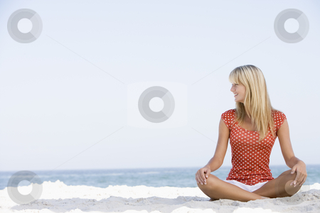 Young woman relaxing on beach stock photo, Young woman relaxing on beach with ocean in background by Monkey Business Images