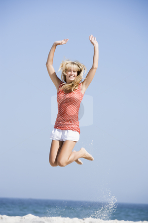 Woman jumping on beach stock photo,  by Monkey Business Images