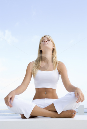 Woman meditating outside stock photo, Woman meditating outside against blue sky by Monkey Business Images