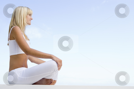 Young woman relaxing outside stock photo, Young woman relaxing outside against blue sky by Monkey Business Images