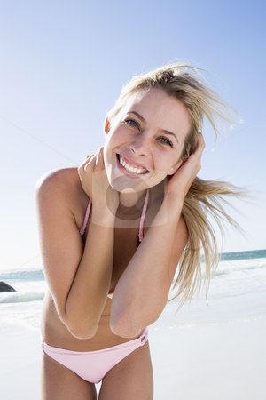Young woman relaxing on beach stock photo, Young woman relaxing on beach wearing bikini by Monkey Business Images