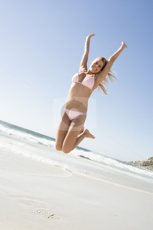 Young woman leaping on beach stock photo, Woman wearing bikini leaping on beach by Monkey Business Images