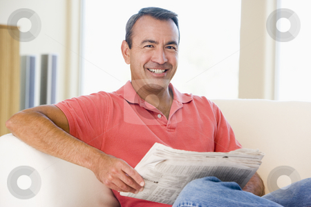 Man reading newspaper in living room smiling