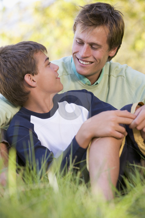 Man and young boy sitting outdoors smiling stock photo,  by Monkey Business Images