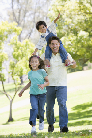 Man with two young children running outdoors smiling stock photo,  by Monkey Business Images