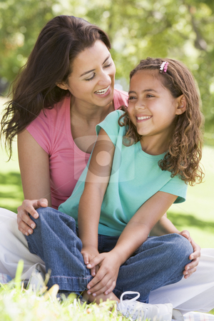 Woman and young girl sitting outdoors smiling stock photo,  by Monkey Business Images