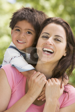 Woman and young boy embracing outdoors smiling stock photo,  by Monkey Business Images