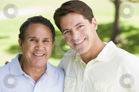 Two men standing outdoors smiling stock photo,  by Monkey Business Images