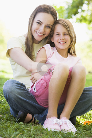 Woman and young girl outdoors embracing and smiling stock photo,  by Monkey Business Images