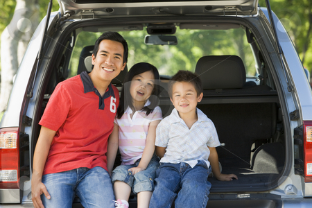 Man with two children sitting in back of van smiling stock photo,  by Monkey Business Images
