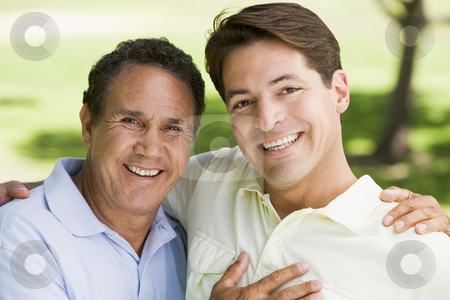 Two men outdoors embracing and smiling stock photo,  by Monkey Business Images