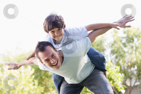 Man and young boy outdoors playing airplane smiling stock photo,  by Monkey Business Images