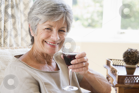 Woman in living room with glass of wine smiling stock photo,  by Monkey Business Images