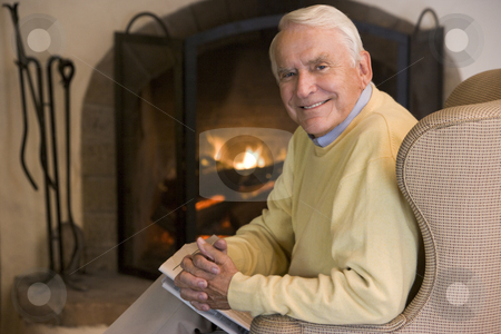 Man in living room with newspaper smiling stock photo,  by Monkey Business Images