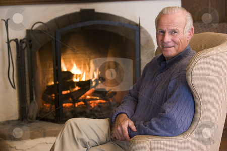 Man sitting in living room by fireplace smiling stock photo,  by Monkey Business Images