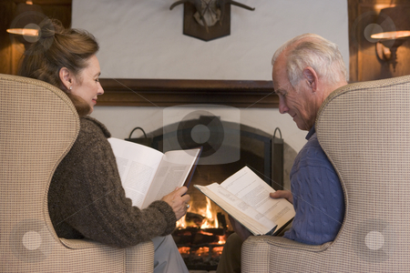 Couple sitting in living room by fireplace reading stock photo,  by Monkey Business Images