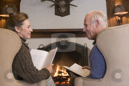 Couple sitting in living room by fireplace with books smiling stock photo,  by Monkey Business Images